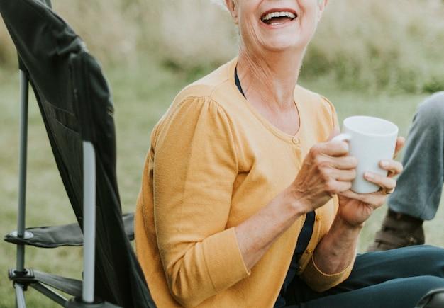 Vrolijke hogere vrouw die van een mok koffie geniet