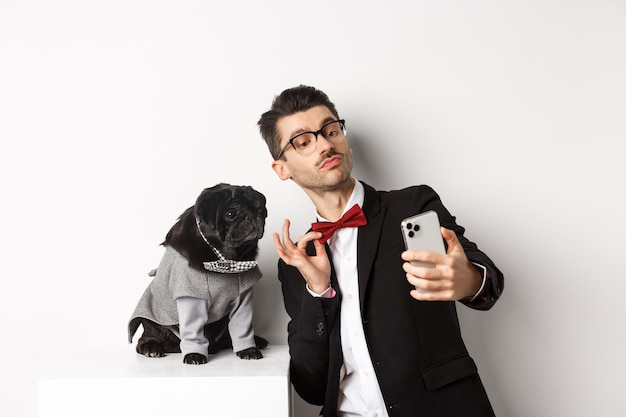 Vrolijke hondenbezitter in pak nieuwjaar vieren met hond, selfie nemen op smartphone in de buurt van schattige zwarte mops in kostuum, wit.