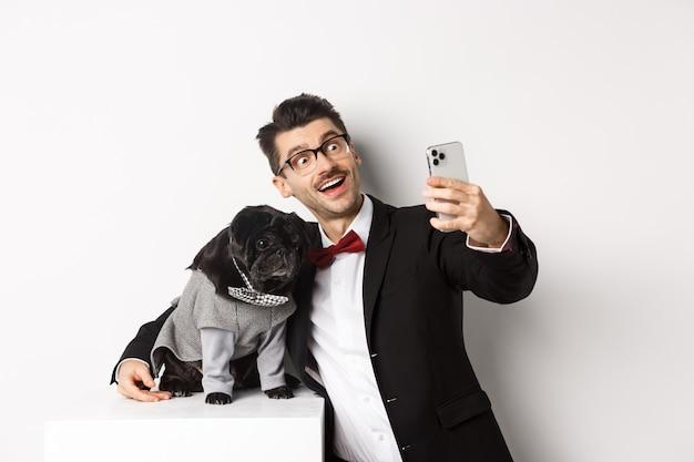 Vrolijke hondeneigenaar in pak kerstmis vieren met hond, selfie nemen op smartphone en schattige zwarte mops knuffelen in kostuum, wit.