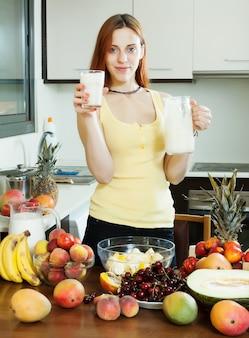Vrolijke huisvrouw drinken melkcocktail met vruchten