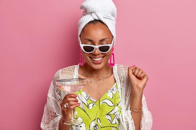 Vrolijke huisvrouw heeft plezier op pyjamafeestje, steekt gebalde vuist op, viert een speciale gebeurtenis, drinkt cocktail, draagt een badhanddoek op het hoofd, zonnebril, giechelt positief, geïsoleerd over roze muur