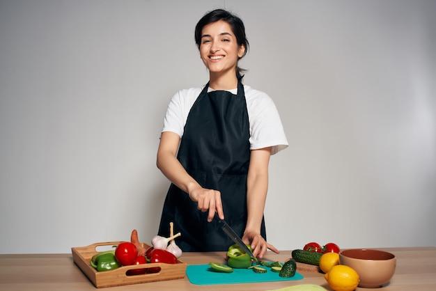 Vrolijke huisvrouw in zwarte schorten groenten eten koken