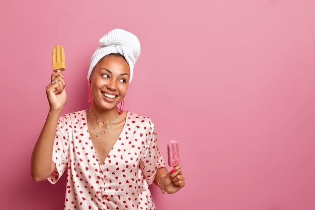 Vrolijke huisvrouw met een donkere huid rillingen thuis met lekker ijs danst zorgeloos heeft een goed humeur gekleed in zijden pyjama draagt een badhanddoek op het hoofd geïsoleerd over roze muur lege ruimte opzij