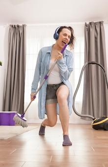 Vrolijke huisvrouw zingt terwijl ze het huis schoonmaakt