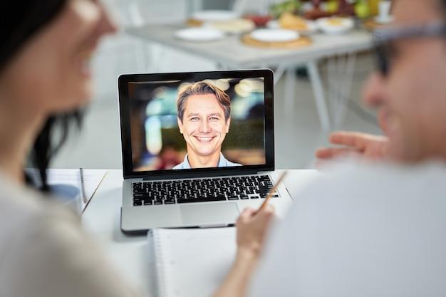 Vrolijke huwelijksconsulent lacht naar zijn klanten, gebruikt de videochat-app en geeft hulp tijdens de lockdown. online overlegconcept. focus op laptopscherm