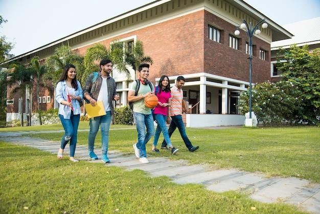 Vrolijke indiase aziatische jonge groep studenten of vrienden die samen lachen terwijl ze op de campus zitten, staan of lopen