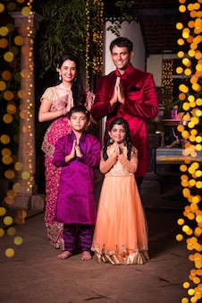 Vrolijke indiase familie verwelkomt op diwali-avond buiten huis met diwali-verlichting, indisch stel en kinderen of mensen in namaskar poseren verwelkomende gasten op diwali-feest of festivalnacht