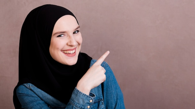 Vrolijke islamitische vrouw die haar vinger op iets richt
