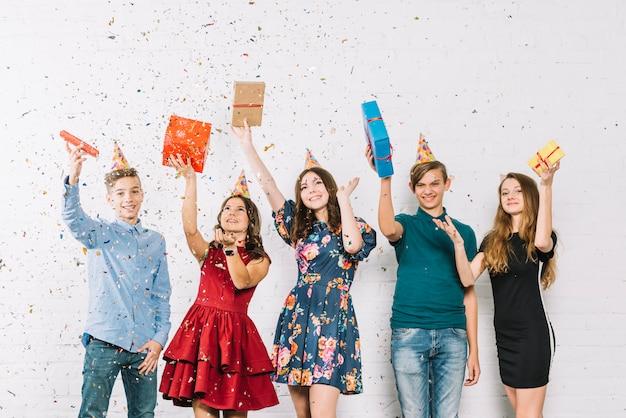 Vrolijke jeugdvrienden overladen met het gooien van confetti op verjaardagsfeestje