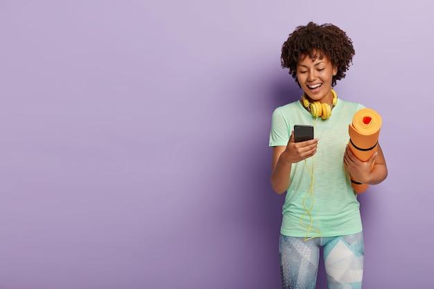 Vrolijke jong meisje heeft pauze in opleiding, poses met fitness mat, smartphone houdt, geniet van liedjes in hoofdtelefoons