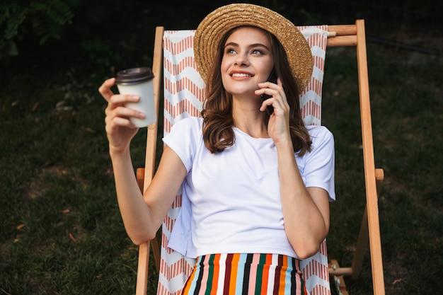 Vrolijke jong meisje rusten op een hangmat in het stadspark buiten in de zomer, afhaalmaaltijden koffie drinken, praten op mobiele telefoon