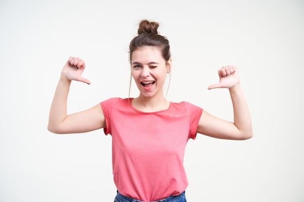 Vrolijke jonge aantrekkelijke bruinharige dame die vrolijk naar de camera knipoogt terwijl ze zichzelf laat zien met opgeheven duimen, geïsoleerd tegen een witte achtergrond