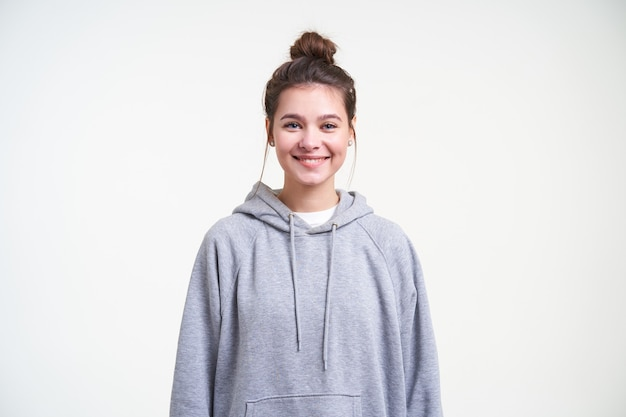 Vrolijke jonge aantrekkelijke bruinharige vrouw met natuurlijke make-up die graag naar de camera kijkt met een charmante glimlach terwijl ze tegen een witte achtergrond staat
