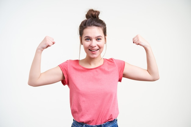 Vrolijke jonge aantrekkelijke bruinharige vrouw met natuurlijke make-up die haar handen opheft terwijl ze biceps toont en graag lacht naar de camera, geïsoleerd op witte achtergrond