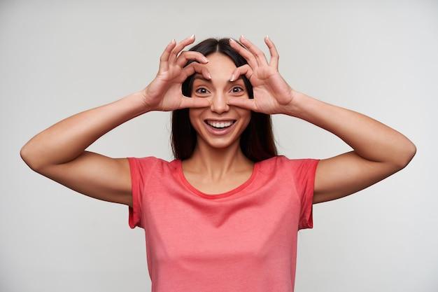 Vrolijke jonge aantrekkelijke bruinogige brunette dame met natuurlijke make-up handen opheffen naar haar gezicht en plezier tijdens het poseren in vrijetijdskleding
