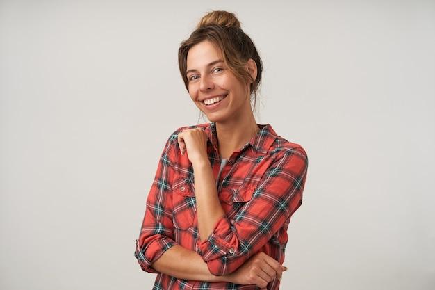 Vrolijke jonge aantrekkelijke brunette met groene ogen die gelukkig camera met charmante glimlach bekijkt terwijl status over witte achtergrond in vrijetijdskleding