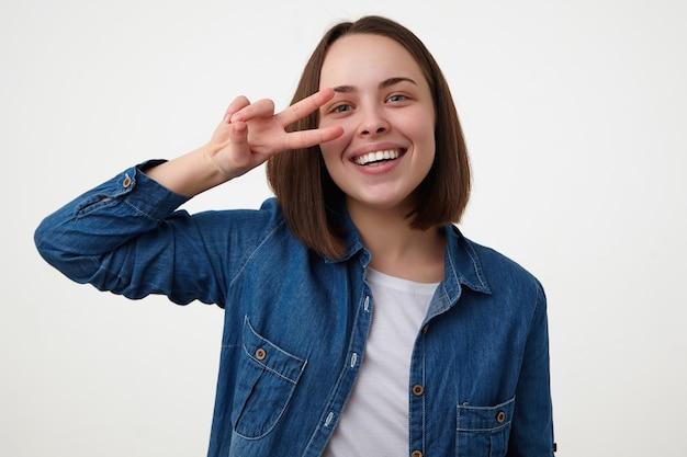 Vrolijke jonge aantrekkelijke donkerharige vrouw die graag naar de camera glimlacht en vredesgebaar in de buurt van haar gezicht houdt, staande op een witte achtergrond in vrijetijdskleding