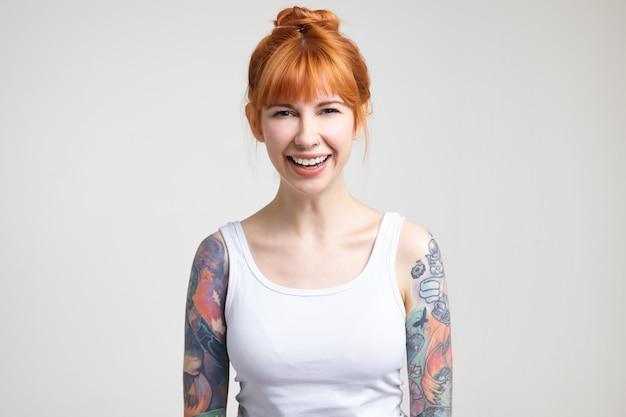 Vrolijke jonge aantrekkelijke getatoeëerde vrouw met foxy haar die gelukkig lacht terwijl ze vrolijk naar de camera kijkt, staande op een witte achtergrond met handen naar beneden