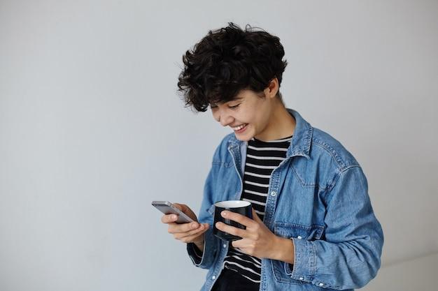 Vrolijke jonge aantrekkelijke kortharige krullende vrouw die thee drinkt en haar sociale netwerken controleert terwijl ze op een witte achtergrond staat, vrolijk lacht terwijl ze naar het scherm van haar telefoon kijkt