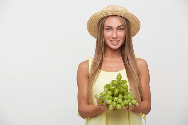 Vrolijke jonge aantrekkelijke langharige blonde vrouw met casual kapsel lachend oprecht en met groene druiven in opgeheven handen, staande tegen een witte achtergrond