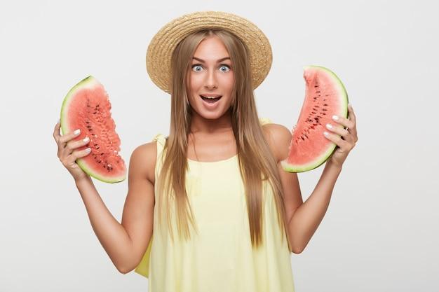 Vrolijke jonge aantrekkelijke langharige blonde vrouw met natuurlijke make-up rond haar blauwe ogen terwijl ze verbaasd naar de camera kijkt, staande op een witte achtergrond met plakjes watermeloen