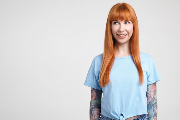 Vrolijke jonge aantrekkelijke langharige roodharige dame met casual kapsel glimlachend wijd terwijl ze graag opzij kijkt, poseren op witte achtergrond in blauw t-shirt