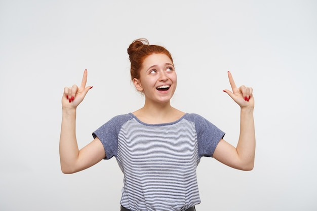 Vrolijke jonge aantrekkelijke roodharige vrouw met natuurlijke make-up naar boven gericht met opgeheven wijsvingers en breed glimlachend, geïsoleerd over witte muur