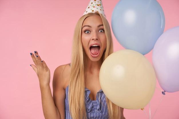Vrolijke jonge aantrekkelijke vrouw met lang blond haar casual kapsel met gelukkige reactie op het krijgen van geweldig cadeau, poseren in veelkleurige lucht ballonnen terwijl staande op roze achtergrond