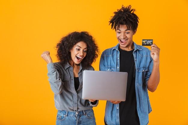 Vrolijke jonge afrikaanse paar staande geïsoleerd, met laptop computer, vieren, plastic creditcard tonen