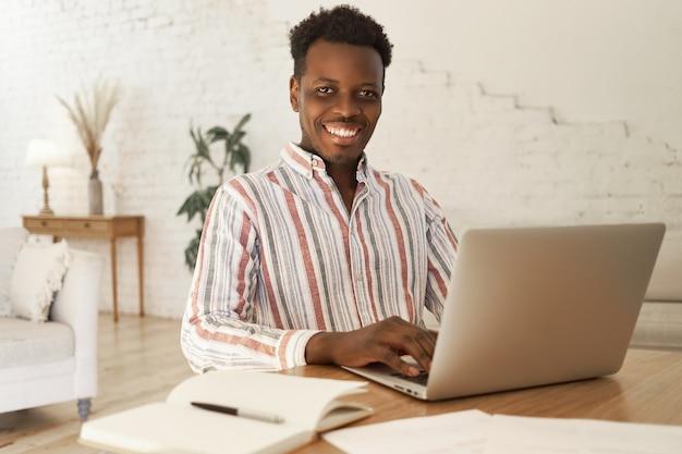 Vrolijke jonge afrikaanse student zittend aan tafel in een gezellige woonkamer met behulp van laptop voor studeren via online platform, notities maken in beurt.