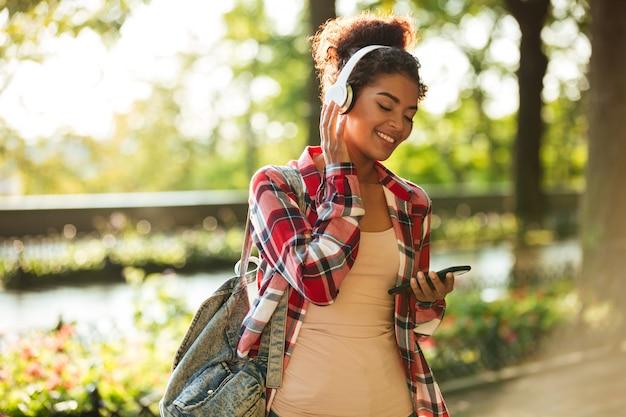 Vrolijke jonge afrikaanse vrouw die in openlucht loopt