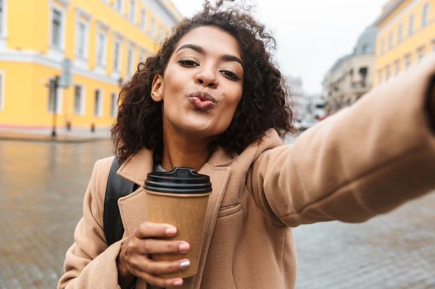 Vrolijke jonge afrikaanse vrouw die jas draagt die buiten loopt, afhaalmaaltijdenkoffie houdt, die een selfie neemt
