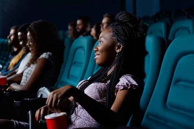 Vrolijke jonge afrikaanse vrouw die lacht terwijl u geniet van een film in de lokale bioscoop