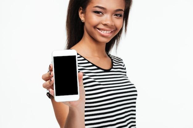 Vrolijke jonge afrikaanse vrouw die vertoning van telefoon toont.
