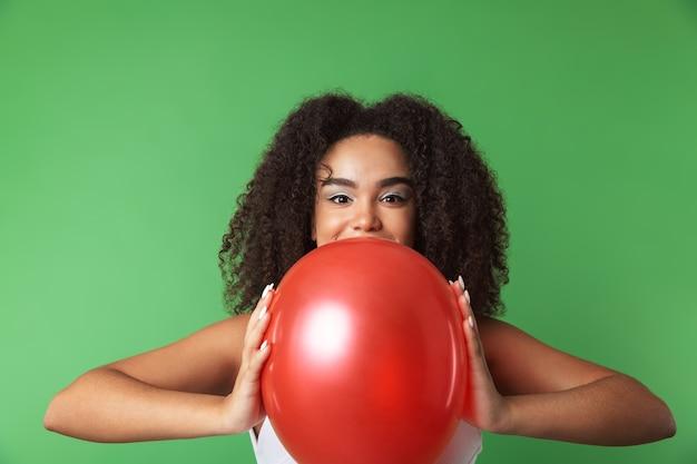Vrolijke jonge afrikaanse vrouw, gekleed in jurk vieren, ballon geïsoleerd te houden