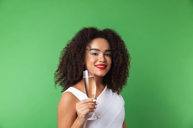 Vrolijke jonge afrikaanse vrouw, gekleed in jurk vieren geïsoleerd, champagne drinken uit een glas