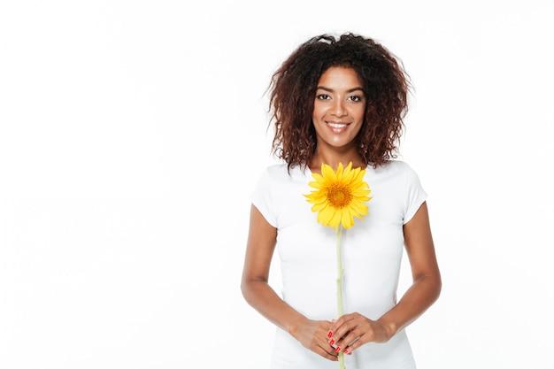 Vrolijke jonge afrikaanse vrouw met bloem.
