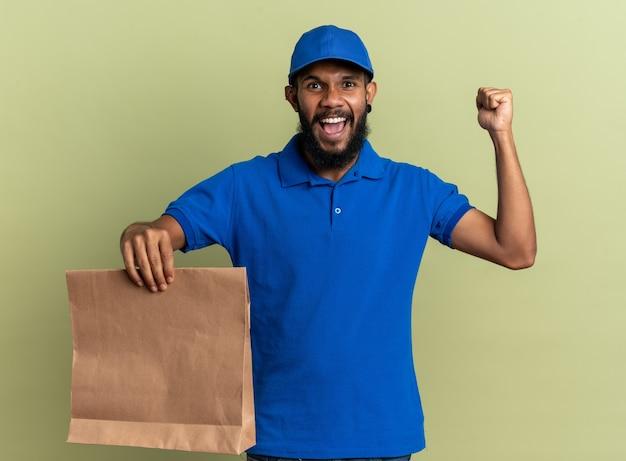 Vrolijke jonge afro-amerikaanse bezorger die voedselpakket vasthoudt en vuist omhoog houdt geïsoleerd op olijfgroene achtergrond met kopieerruimte