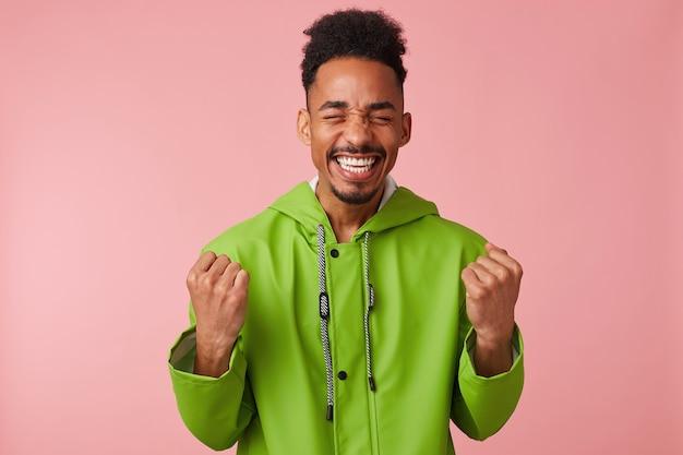 Vrolijke jonge afro-amerikaanse knappe kerel staat op, balde zijn vuisten, breed glimlachend en absoluut gelukkig - hij won de loterij!