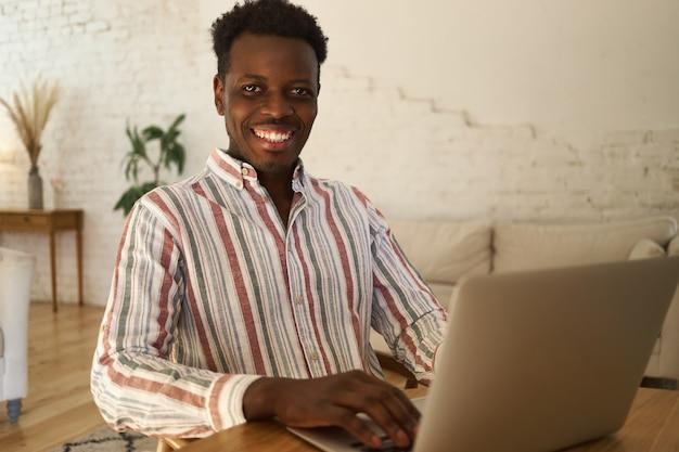 Vrolijke jonge afro-amerikaanse man in gestreept shirt op afstand werken op laptop vanwege sociale afstand, blij om meer tijd thuis door te brengen