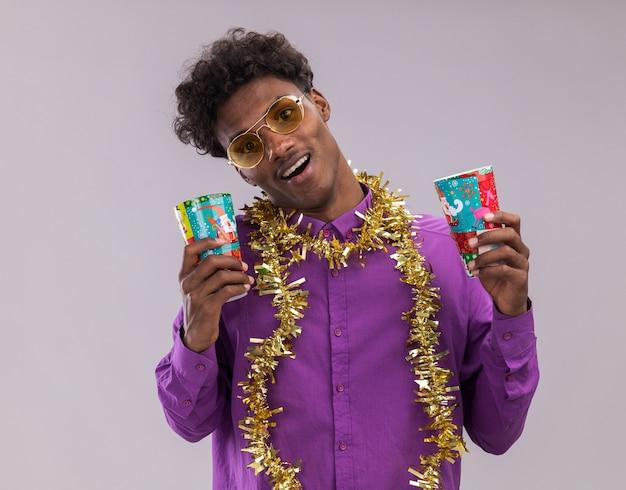 Vrolijke jonge afro-amerikaanse man met bril met klatergoud slinger rond nek met plastic kerstbekers kijken camera geïsoleerd op witte achtergrond