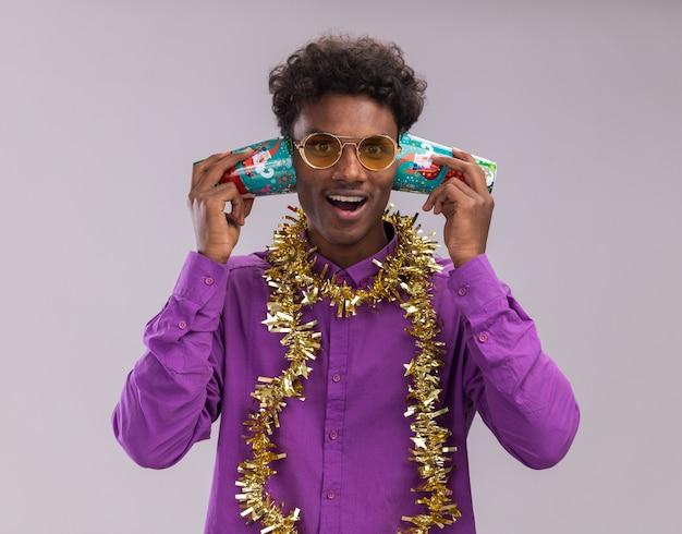 Vrolijke jonge afro-amerikaanse man met bril met klatergoud slinger rond nek met plastic kerstbekers naast oren luisteren naar gesprek kijken camera geïsoleerd op witte achtergrond