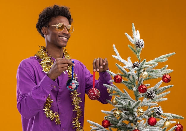 Vrolijke jonge afro-amerikaanse man met bril met klatergoud slinger rond nek staande in de buurt van versierde kerstboom op oranje achtergrond