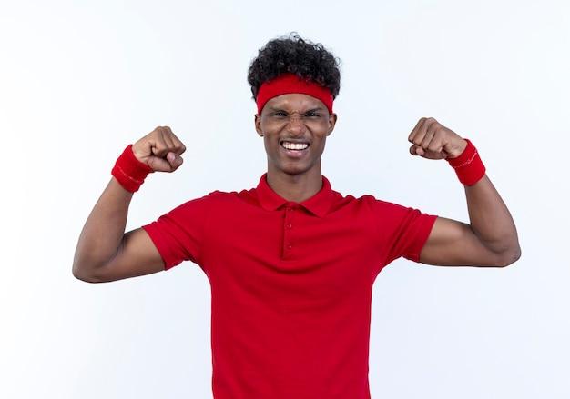 Vrolijke jonge afro-amerikaanse sportieve man met hoofdband en polsbandje doet sterk gebaar geïsoleerd op een witte achtergrond