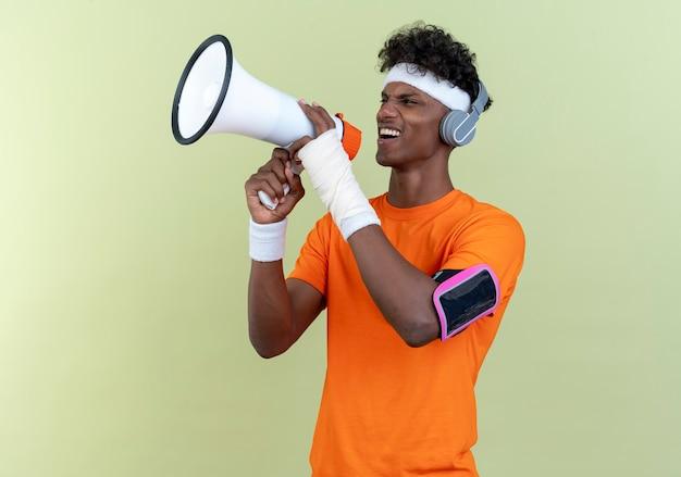 Vrolijke jonge afro-amerikaanse sportieve man met hoofdband en polsbandje en telefoon armband met koptelefoon spreekt op luidspreker geïsoleerd op groene achtergrond