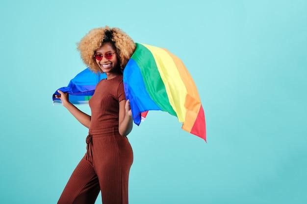 Vrolijke jonge afrovrouw die een trotsvlag over een geïsoleerde achtergrond zwaait. lgbtq-gemeenschapsconcept.