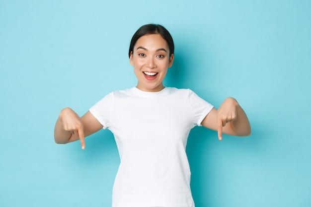 Vrolijke jonge aziatische dame in wit t-shirt wijzende vingers naar beneden en glimlachend opgewonden, op zoek vrolijk terwijl ze de banner demonteert, biedt speciale kortingspromo, staande blauwe achtergrond.