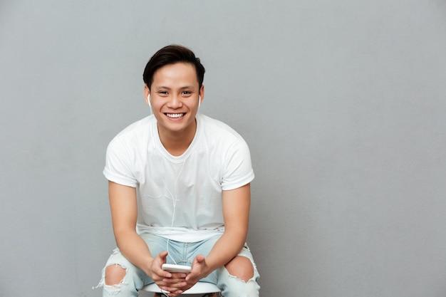 Vrolijke jonge aziatische man luisteren muziek