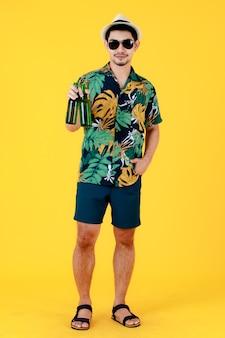 Vrolijke jonge aziatische man met zonnebril glimlachend en het verhogen van een bierflesje. full body studio portret op gele achtergrond. vrolijke en gelukkige mensen in zomervakantie concept.
