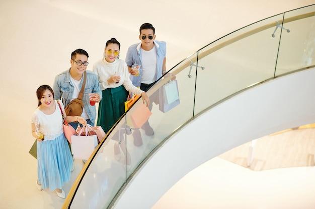 Vrolijke jonge aziatische mensen die zich op balkon van winkelcomplex bevinden en omhoog camera bekijken